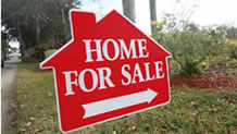 Red home for sale sign on lawn