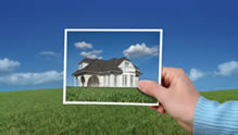Hand holding picture of house against landscape
