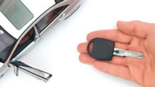 Hand holding car key next to car with open door