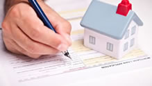 Hand signing mortgage application with small house on document