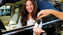 Smiling woman being handed car keys