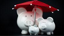 Piggy bank family under red umbrella