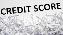 The word 'credit score' over shredded paper.