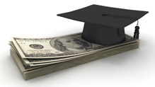 graduation cap on top of a stack of money