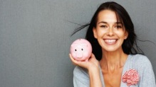 Woman holding pink piggy bank