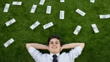 Man lying on grass surrounded by money