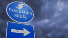 Blue evacuation route sign with arrow