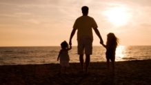 Man and two kids on a beach