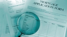 Mortgage application and magnifying glass