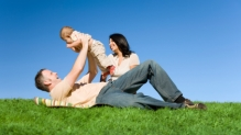 Couple playing with baby on grass