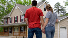 Couple holding hands and looking at home