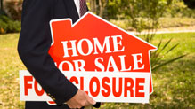 Man in suit holding foreclosure for sale sign