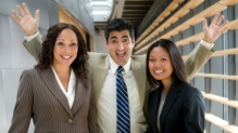 Three office workers, one man standing between two women