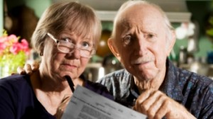 Elderly man and younger woman holding mortgage