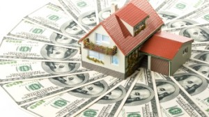 toy house lying on top of fanned out money