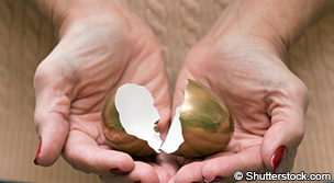 Broken golden egg in palms of hands