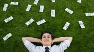 man on grass with cash