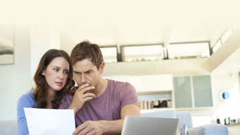 worried couple looking at document