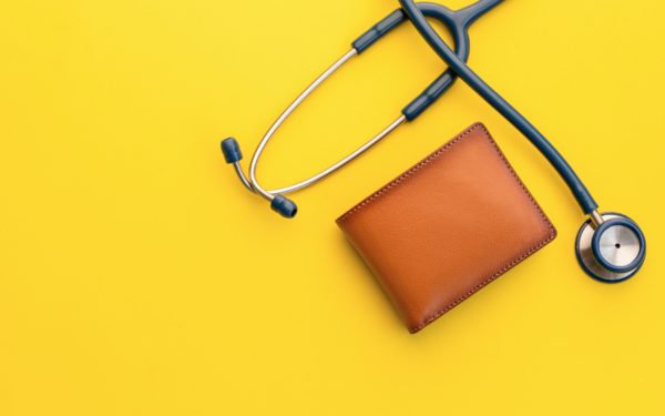 Stethoscope and wallet on yellow background