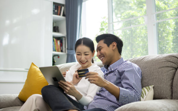 Happy Asian couple shopping online with holding credit card and laptop and sitting at home together, lifestyle concept.