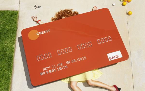 A 39 year old caucasian woman is crushed under a oversized credit card. She is located on her driveway and was crushed while unloading groceries from her car. The card is a life sized prop and there was no compositing in the image.