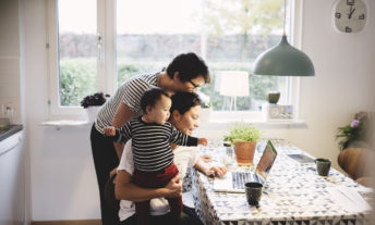 Lesbian couple with daughter looking in laptop at kitchen