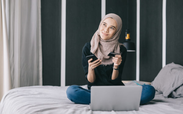 Portrait of young woman wearing a hijab, online shopping with credit card