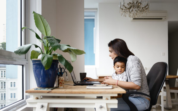 Woman working from a home office desk with her son