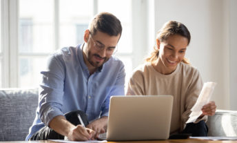 Happy couple using laptop, calculating domestic bills, mortgage or loan documents, smiling woman holding papers, family planning budget, managing household expenses, focused man filling form