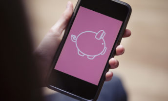 Teenager holding mobile phone with conceptual digital piggy bank on screen