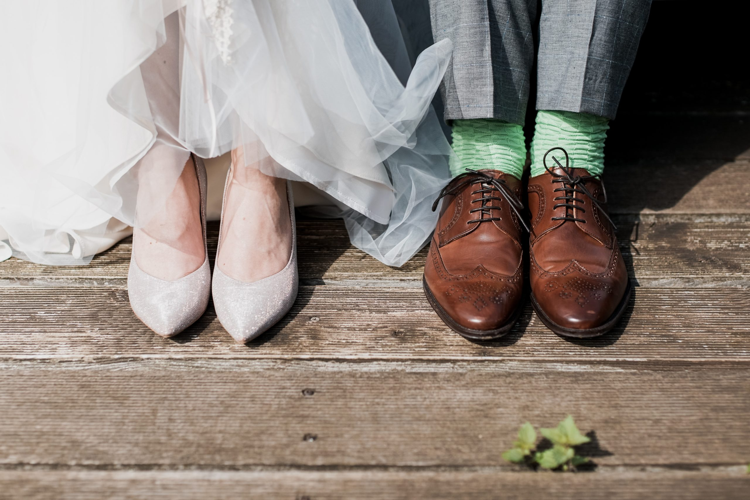 Close-up of a bride and groom standing side-by-side, shot is focused on their shoes standing on a weathered, wood floor
