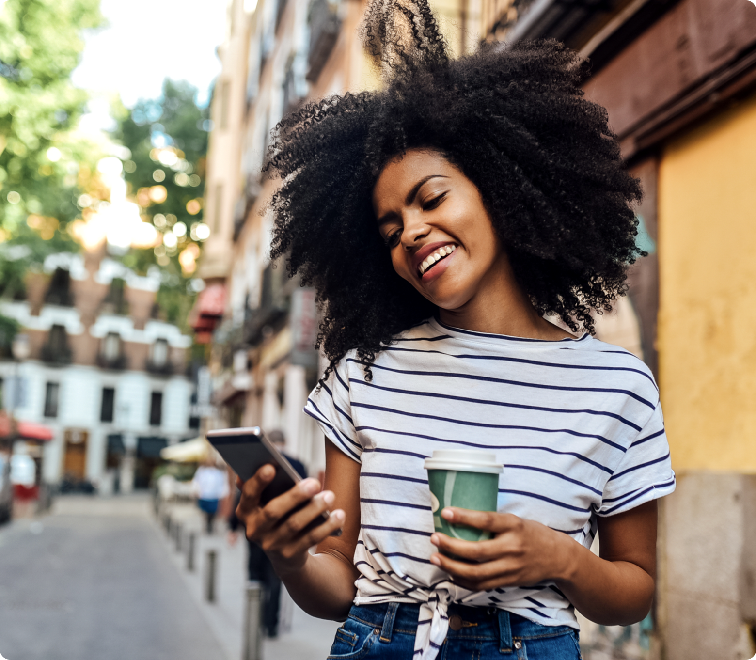 Picture of a girl smiling and looking at her phone